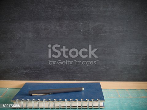 istock Notebooks and pens , Blackboard. (Vintage colors picture) 822173058