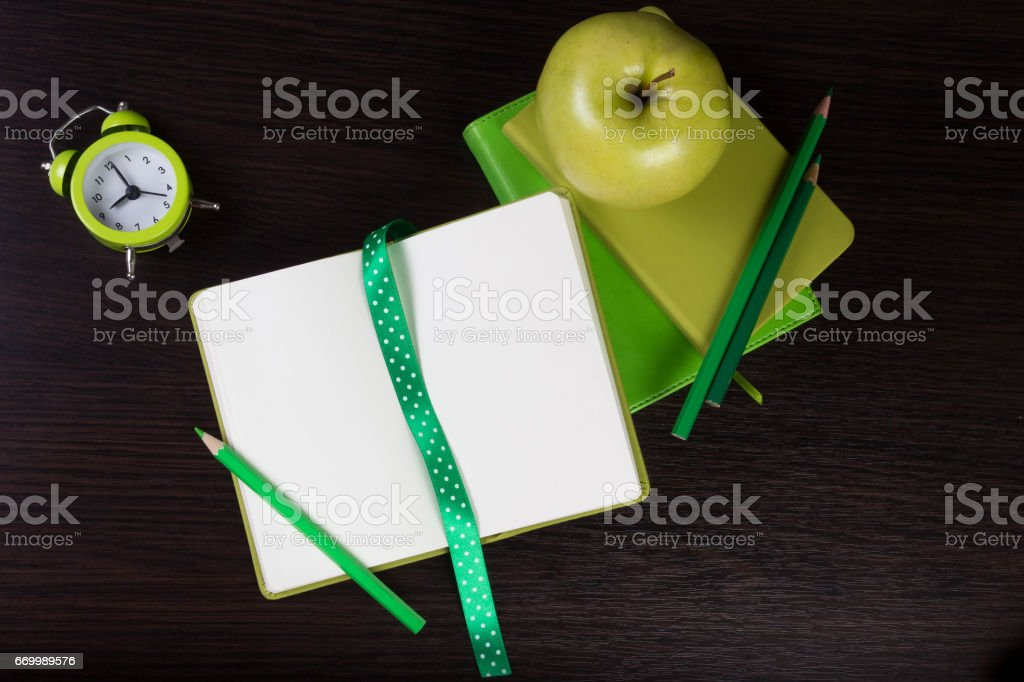Notebooks, pencils, clock and apple on dark wooden background. stock photo