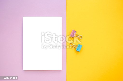 istock Notepad and binder clips on colorful background with copyspace. 1026754868