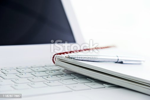 Notepad and pen on computer keyboard.