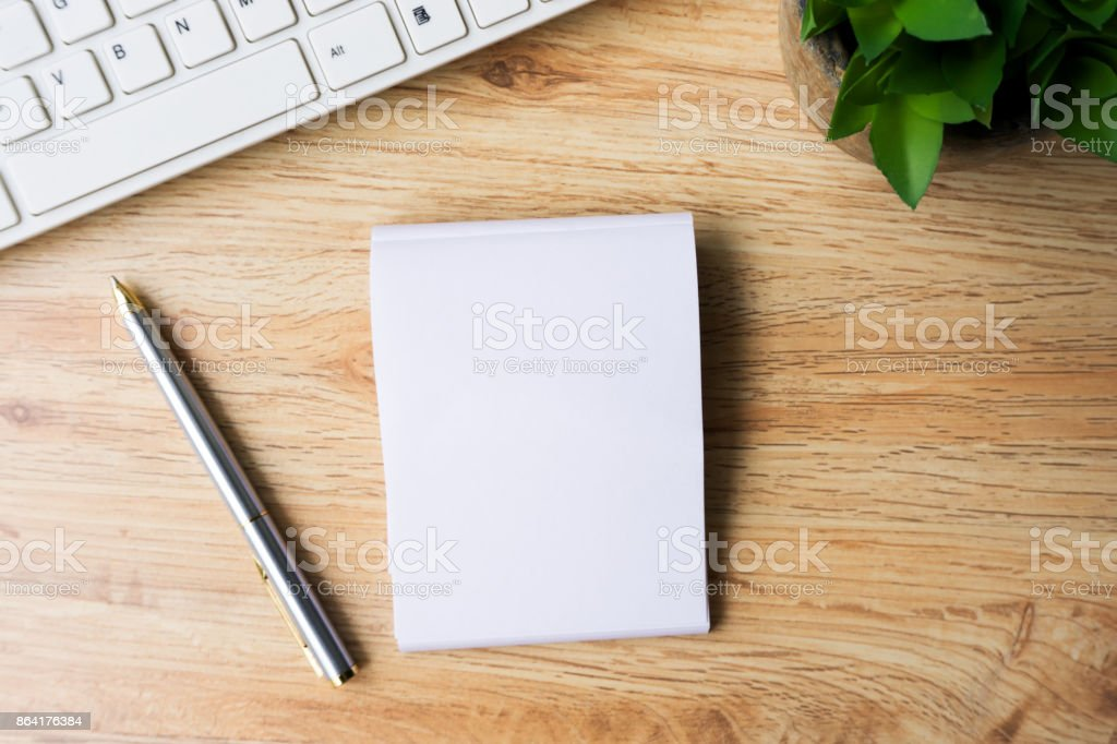 Notepad and Pen with Computer Keyboard on Wood Table royalty-free stock photo