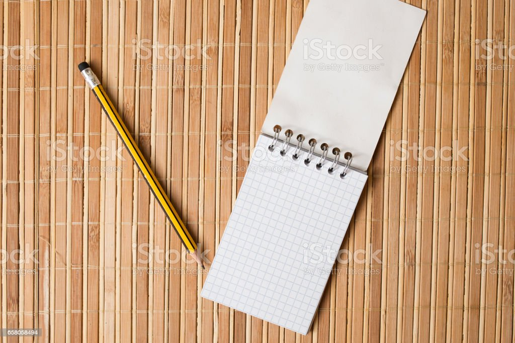Notepad and pencil on a bamboo table stock photo