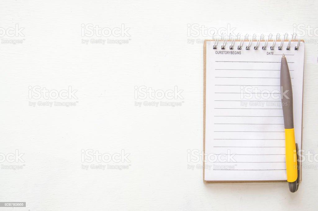 Blocnotes et un crayon sur papier peint de bureau bois