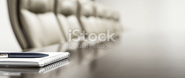 Close-up of notepad kept on table in empty conference room