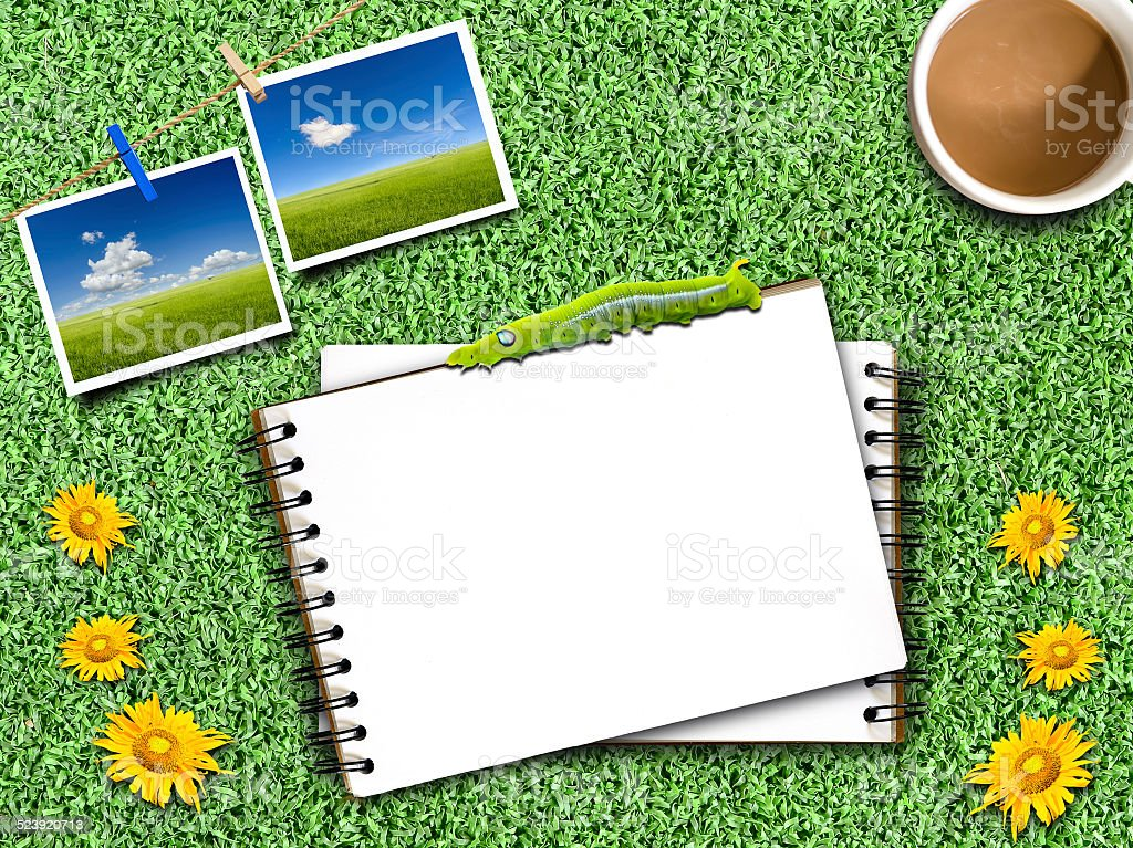Notepad on an artificial Grass with coffee mug, stock photo