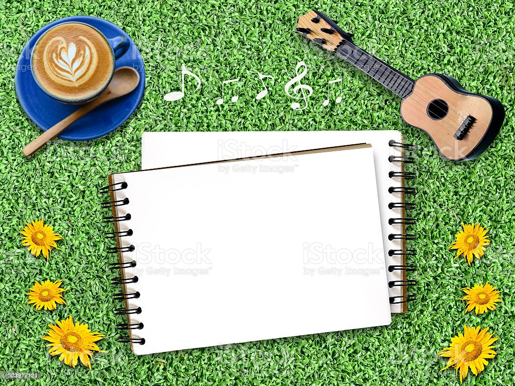 Notepad on an artificial Grass with guitar. stock photo