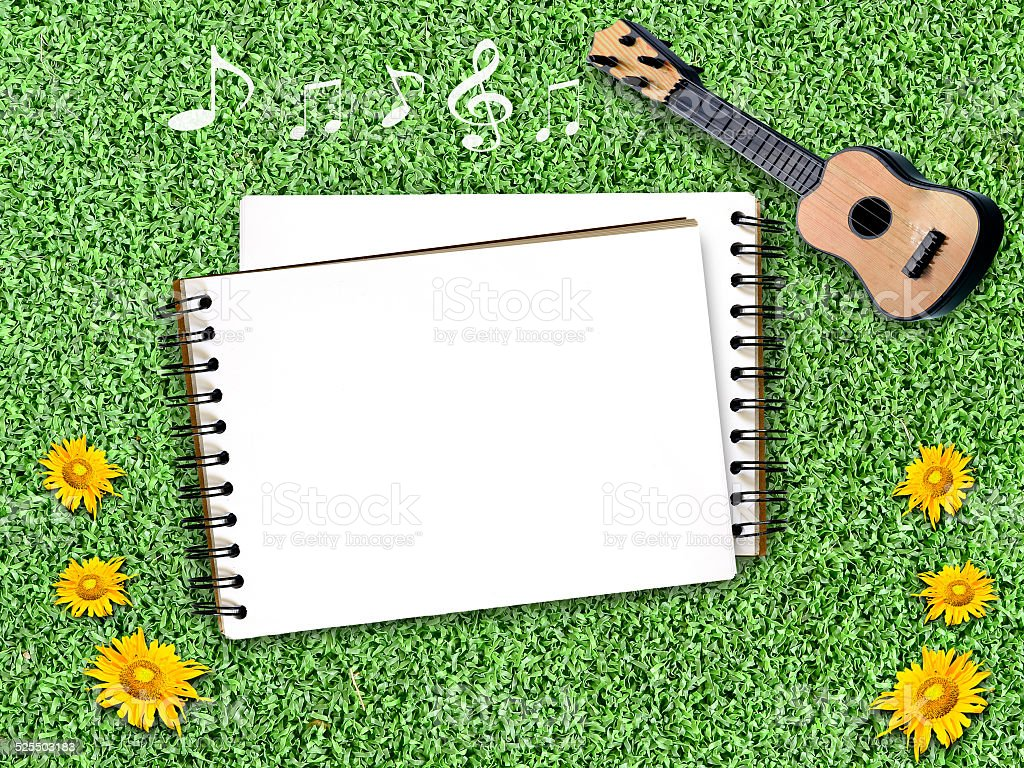 Notepad on an artificial Grass with guitar,pictures and clothesl stock photo