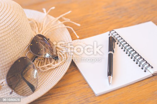 istock Notepad on blank screen with pen,straw hat,sunglasses on wooden desk 961686626