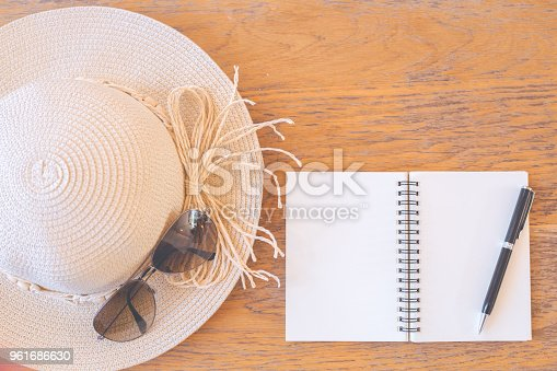 istock Notepad on blank screen with pen,straw hat,sunglasses on wooden desk 961686630
