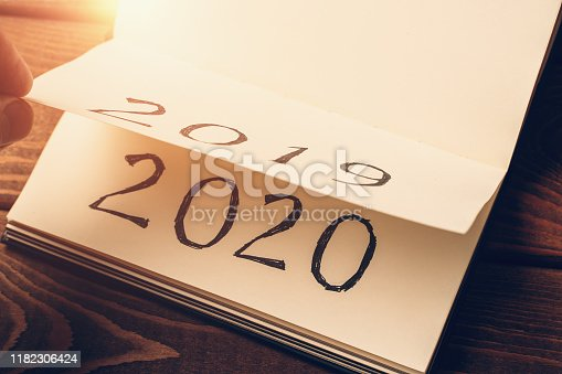 Notepad or calendar with pages and text 2020 and 2019 in sunlight. New year, new beginnings and change concept, toned
