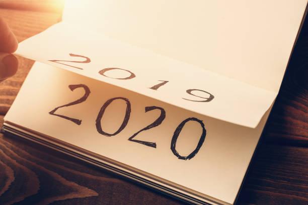 日差しの中でページとテキスト2020と2019とメモ帳やカレンダー。新しい年、新しい始まりとコンセプトの変更 - 終わり ストックフォトと画像