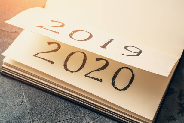 notepad or calendar with pages and text 2020 and 2019 in sunlight. new year, new beginnings and change concept - orthographic symbol stock pictures, royalty-free photos & images