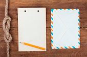 istock Notepad paper, pencil and old envelope on wood 177099052