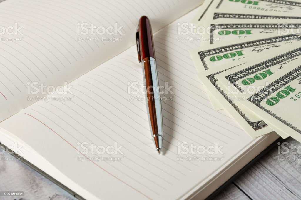Notepad, pen and money on a light wooden background stock photo
