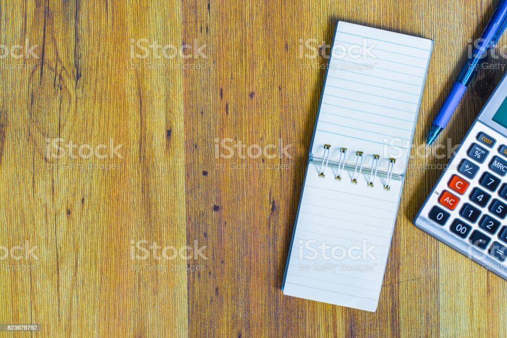 notepad pen calculator and smart phone on wooden table using