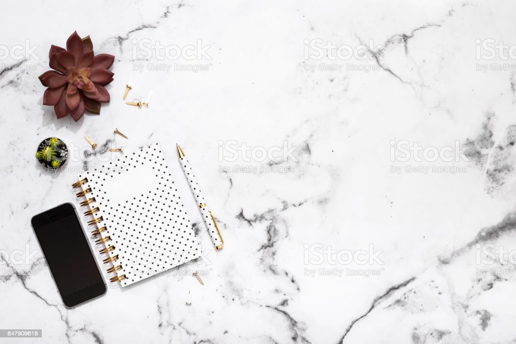 Notepad, pen, mobile phone and office supplies on marble table top stock photo