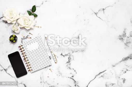 istock Notepad, pen, mobile phone and office supplies on marble table top 847912422