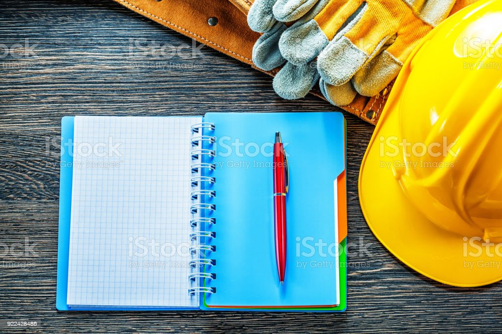 Notepad pen tool belt protective gloves building helmet on woode stock photo