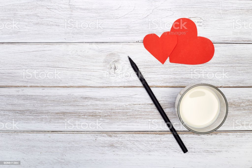 notepad pencil and two red hearts paper with milk stock photo