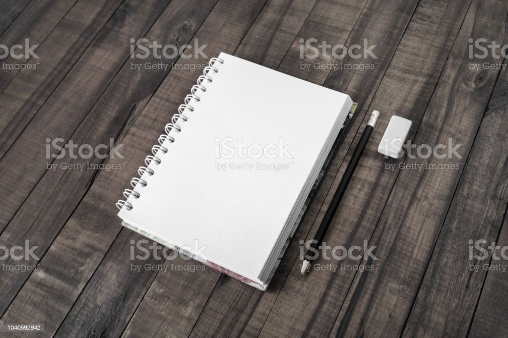 Blank notepad, pencil and eraser on vintage wood background.