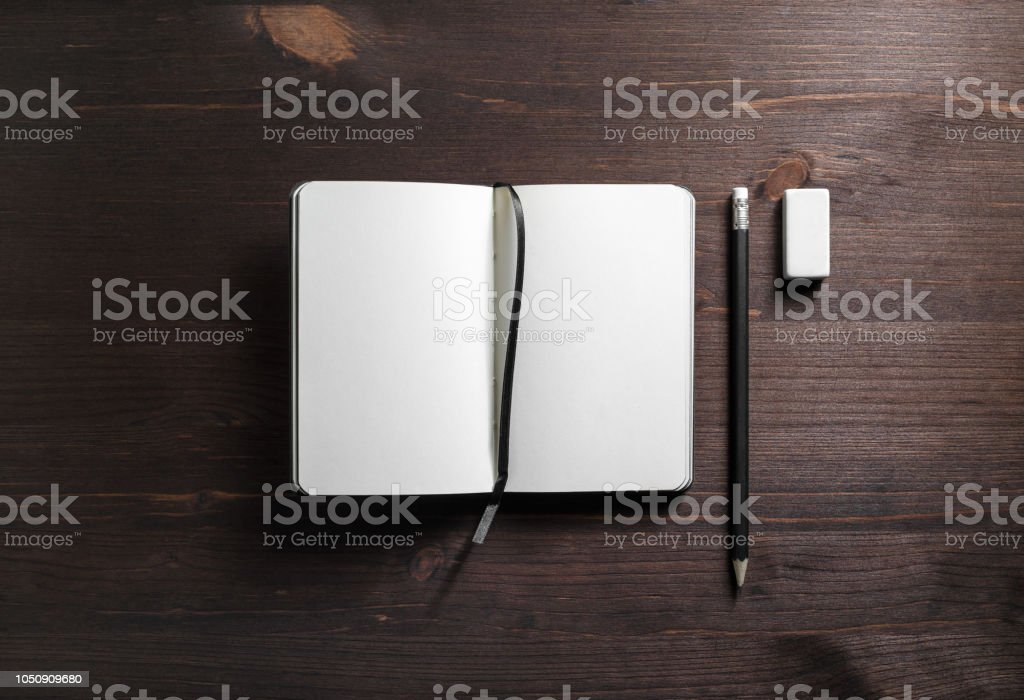 Open notepad, pencil and eraser on wooden background. Template for...