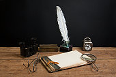 istock Notepad, quill, inkwell, binoculars, magnifying glass, clock, spectacles on table 147506002