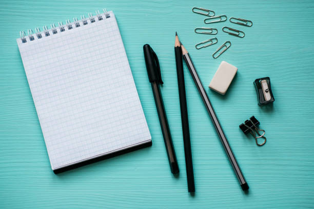 Notepad with a blank page, pen, two pencils, eraser, metal clips on turquoise background stock photo
