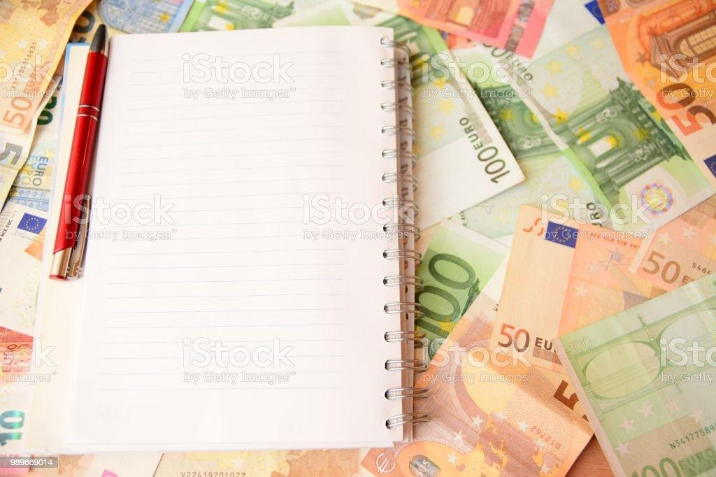 Notepad with a pen, bills, money, savings stock photo