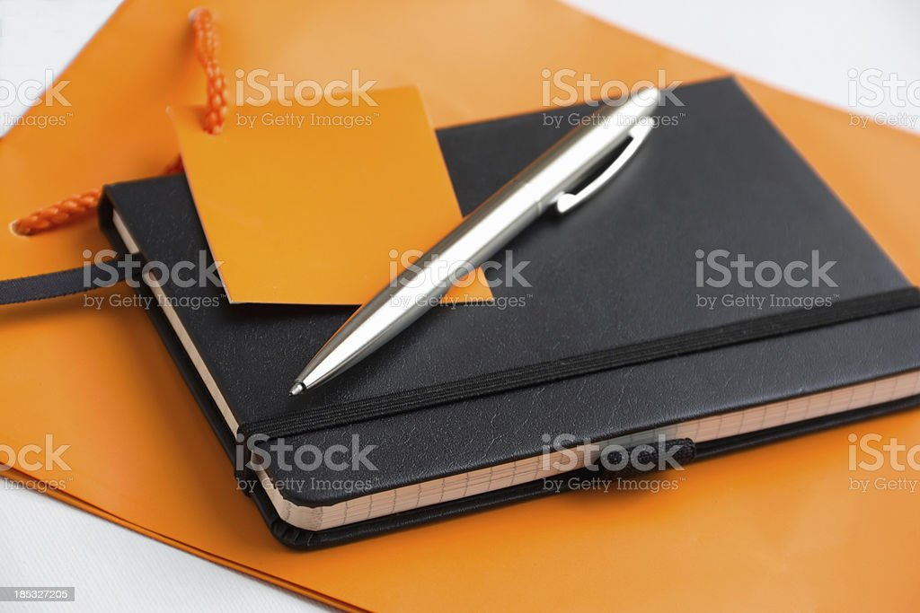 notepad with a pen on an orange bag royalty-free stock photo