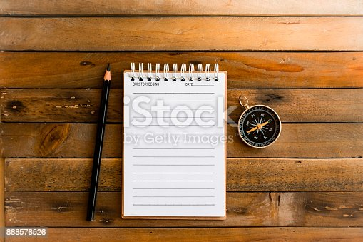 istock notepad with compass on wood board and blurry background. Using wallpaper or background travel or navigator image. 868576526