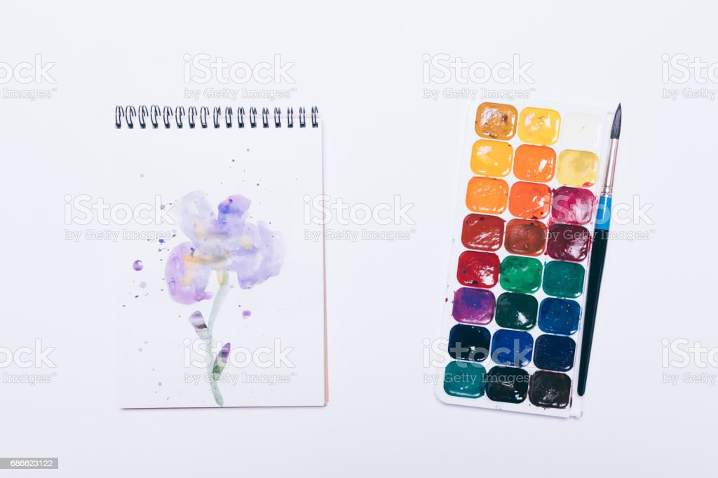 Notepad with drawing of a flower and watercolor on white table royalty-free stock photo