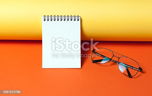 istock Notepad with eye glasses on orange and yellow background. 1031312700