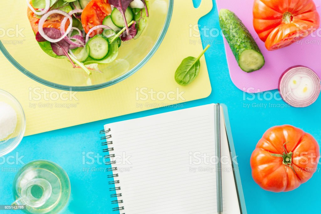 Notepad with fresh biodynamic ingredients for cooking summer salad on blue background, top view. Healthy food background - foto stock