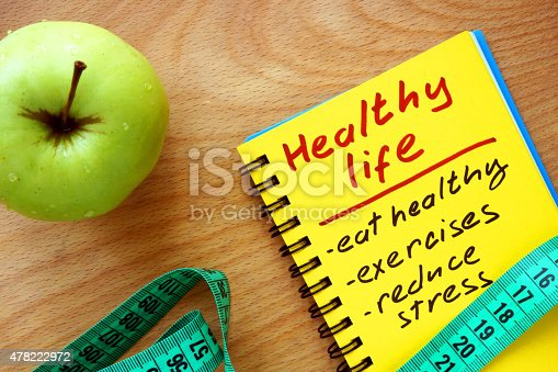 istock Notepad with healthy life guide, apple and measure tape 478222972