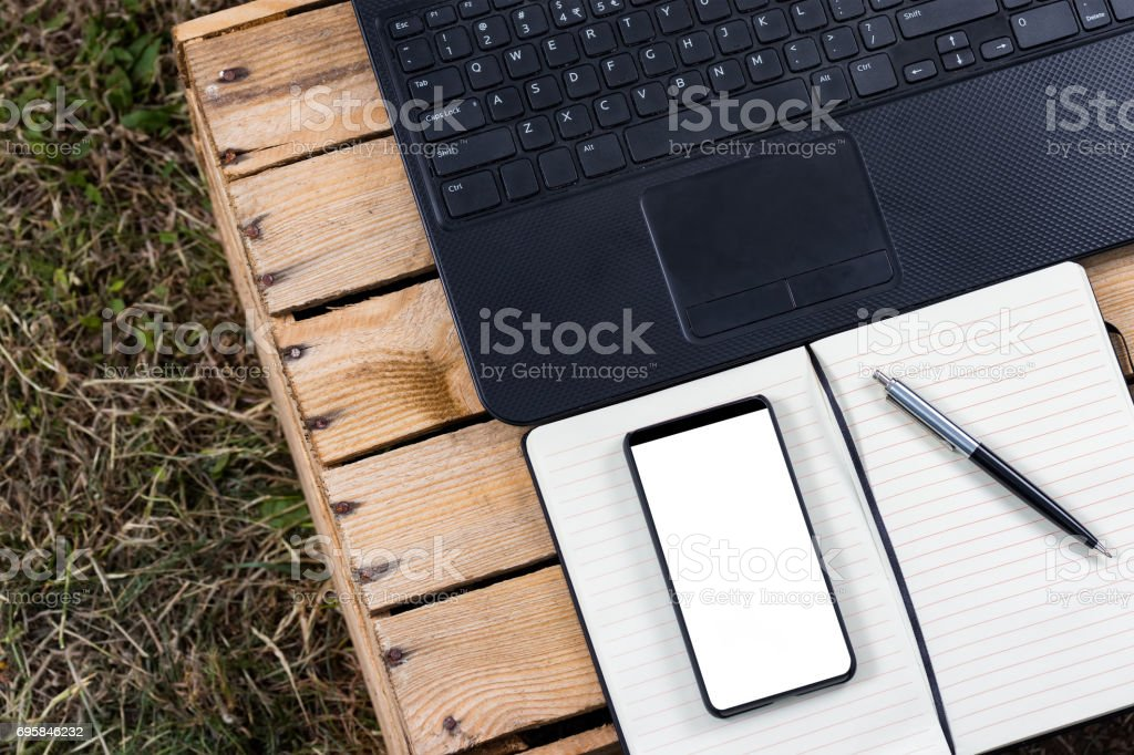 Notepad with laptop and bezel less smartphone with blank screen. stock photo
