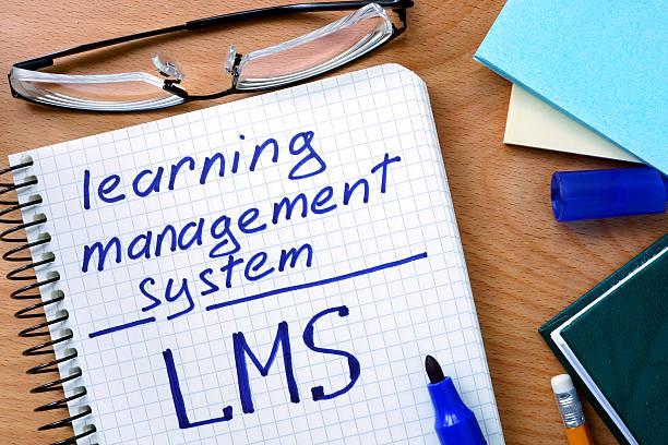 notizblock mit learning management system lms auf office holztisch. - lernfortschrittskontrolle stock-fotos und bilder