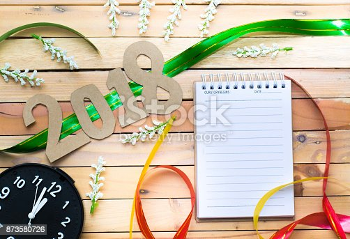 istock notepad with number paper 2018 on wood backgorund for happy new year image. And welcome new year photo. 873580726
