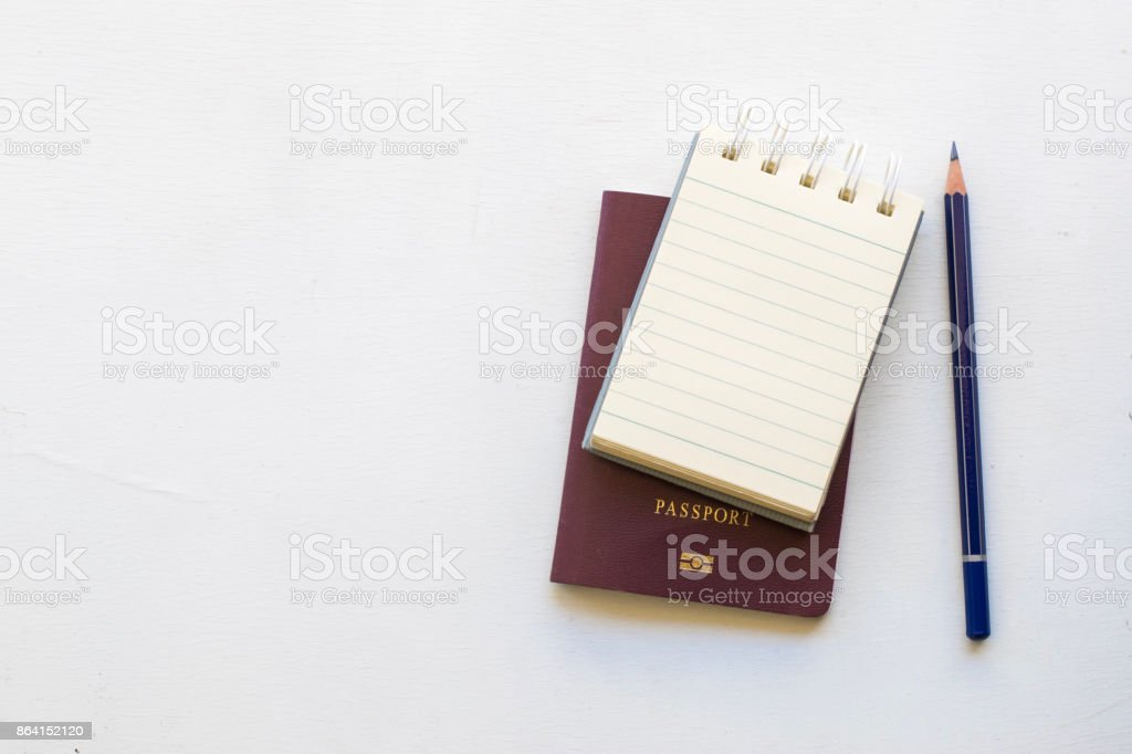 Notepad with passport and smartphone on wood board background.using wallpaper for education, business photo.Take note of the product for book with paper and concept, object or copy space. royalty-free stock photo