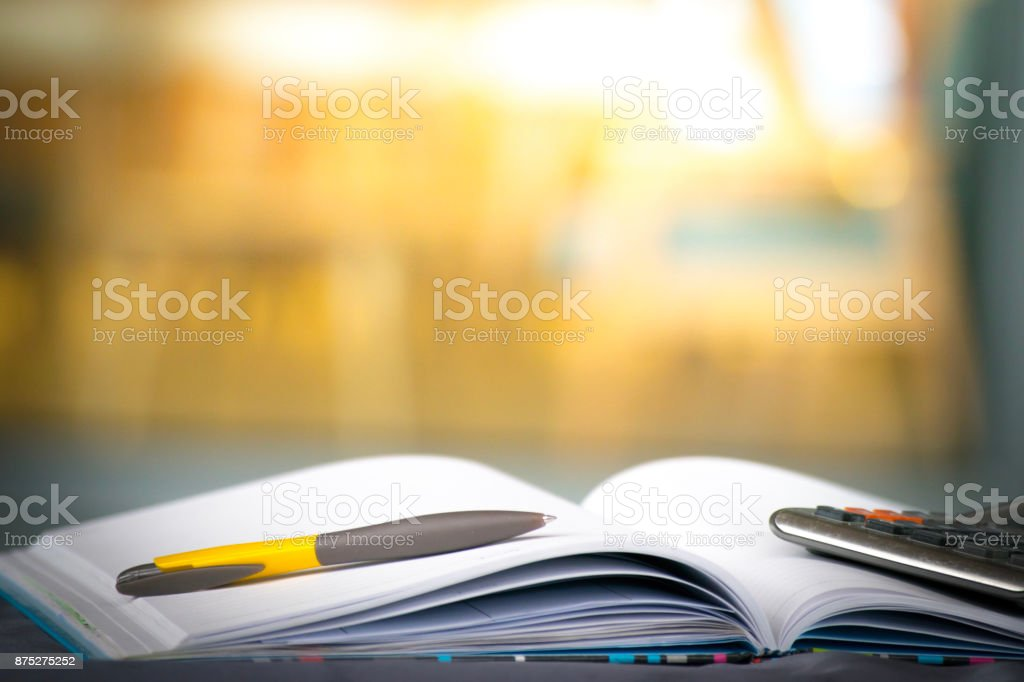 Notepad with pencil and calculator on blurry background.using wallpaper for education, business photo.Take note of the product for book with paper and concept, object or copy space. stock photo