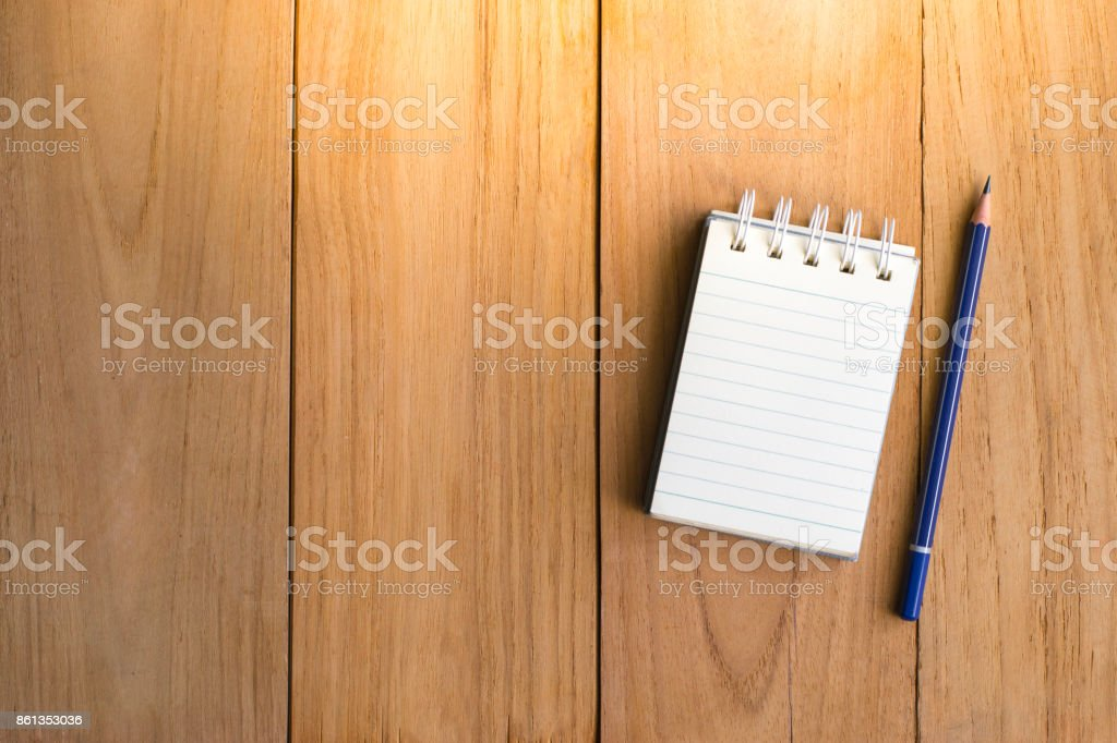 Notepad with pencil on wood board background.using wallpaper for education, business photo.Take note of the product for book with paper and concept, object or copy space. stock photo