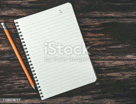 Notepad with yellow pencil placed on old wooden floor vintage style