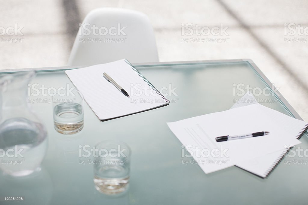 Notepads and pens on conference table stock photo
