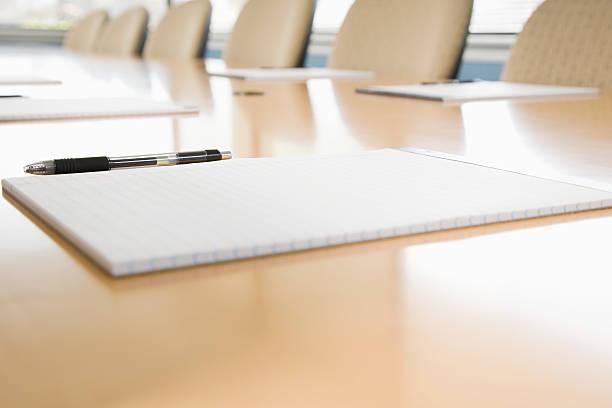 notepads on conference table - instappen stockfoto's en -beelden