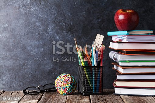 istock Notepads, supplies and glasses in front of chalk board 582311378