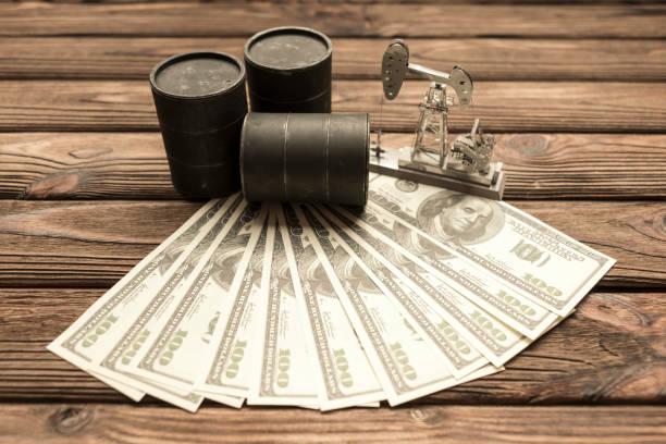 noten von amerikanischen dollar, barrel öl, neftechka auf einem hölzernen hintergrund. - opec stock-fotos und bilder