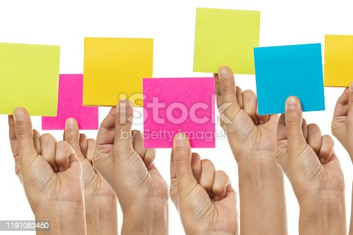 Group of hands are holding colored square papers in a row.