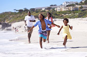 A happy young african family running energetically along the beach