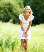 Cute young woman laughing while standing in a field outdoors