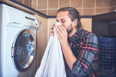 Shot of a young man smelling fresh and clean laundry at home