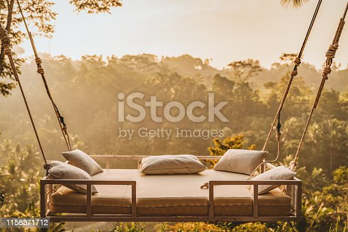 Photo of swing, empty bed hanging over the tropical forest, Bali, Indonesia.